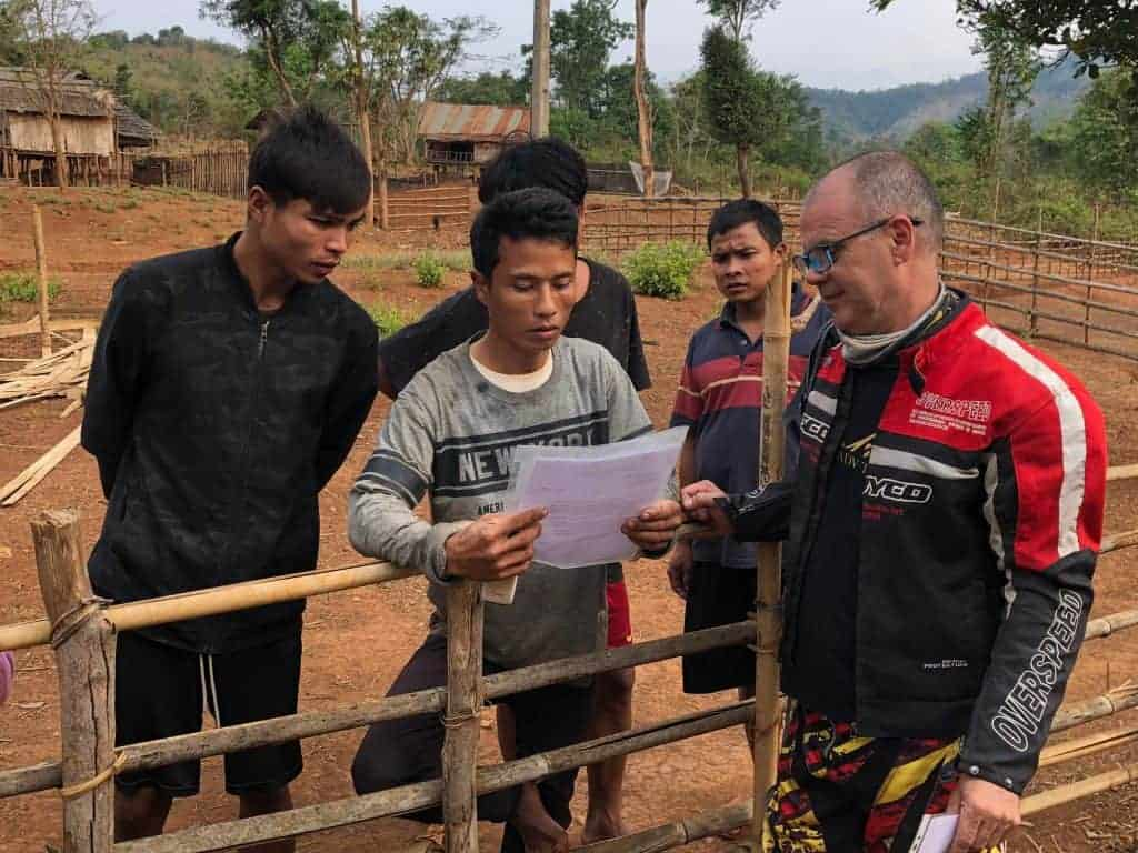 handing-letter-of-introduction-to-villagers-looking-for-crash-sites-along-the-trail-laos
